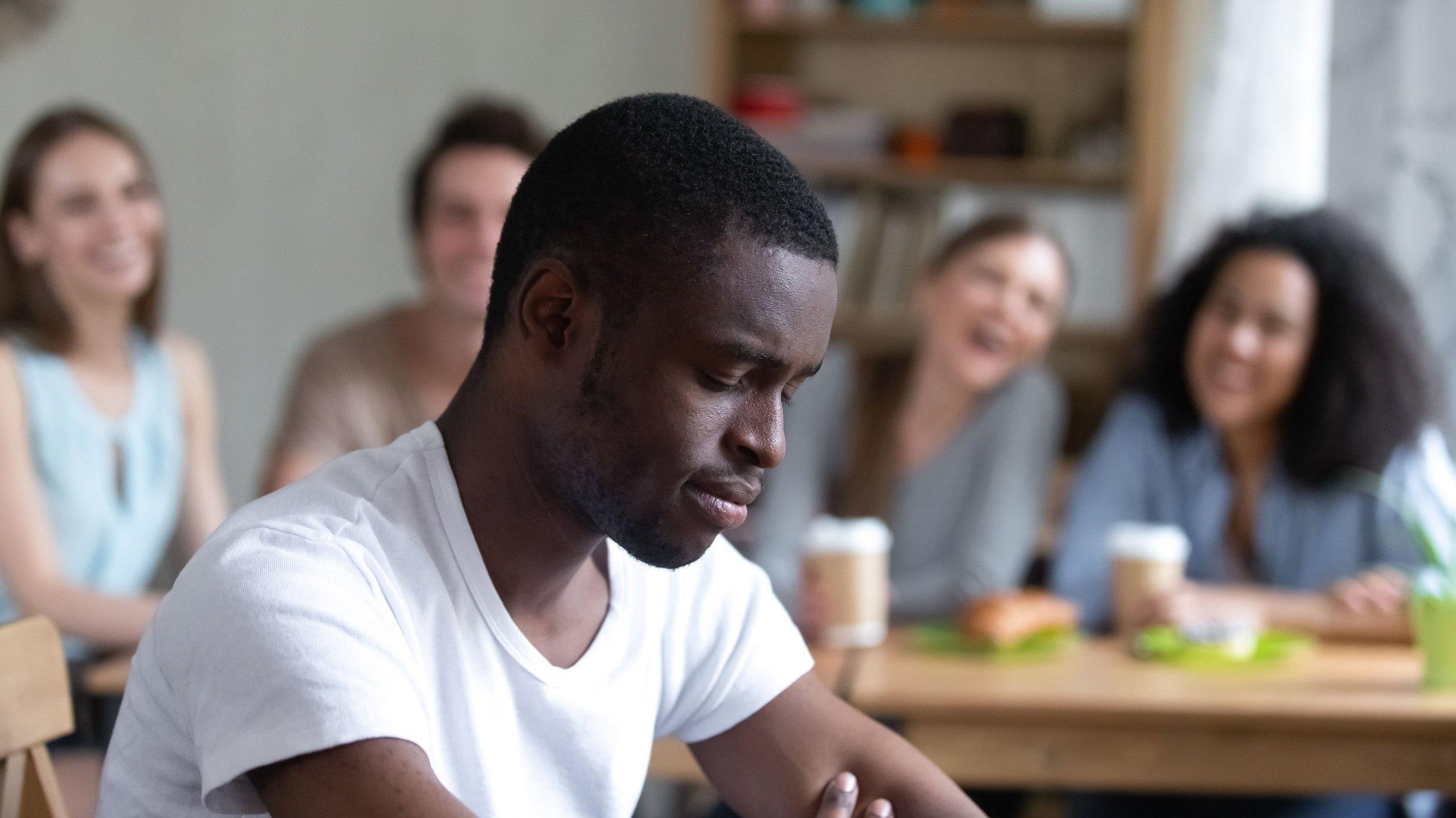 Homem negro com expressão de triste. Mulheres ao fundo rindo.