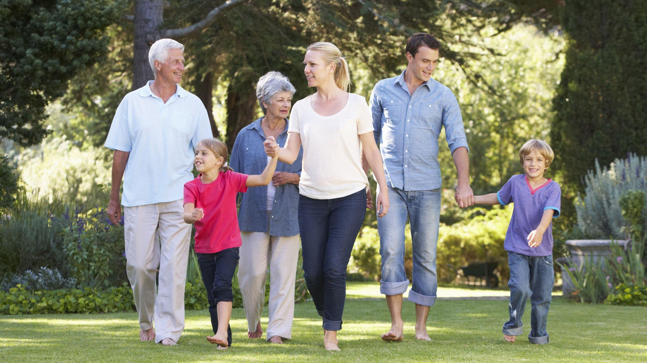 Família feliz, todos sorrindo, caminhando em parque.