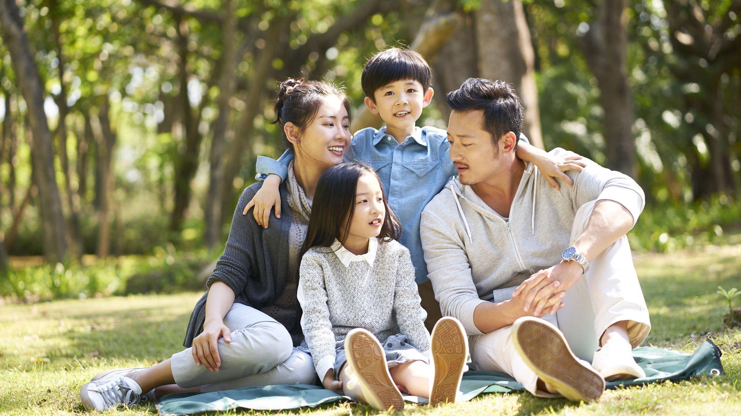 Família asiática em parque.