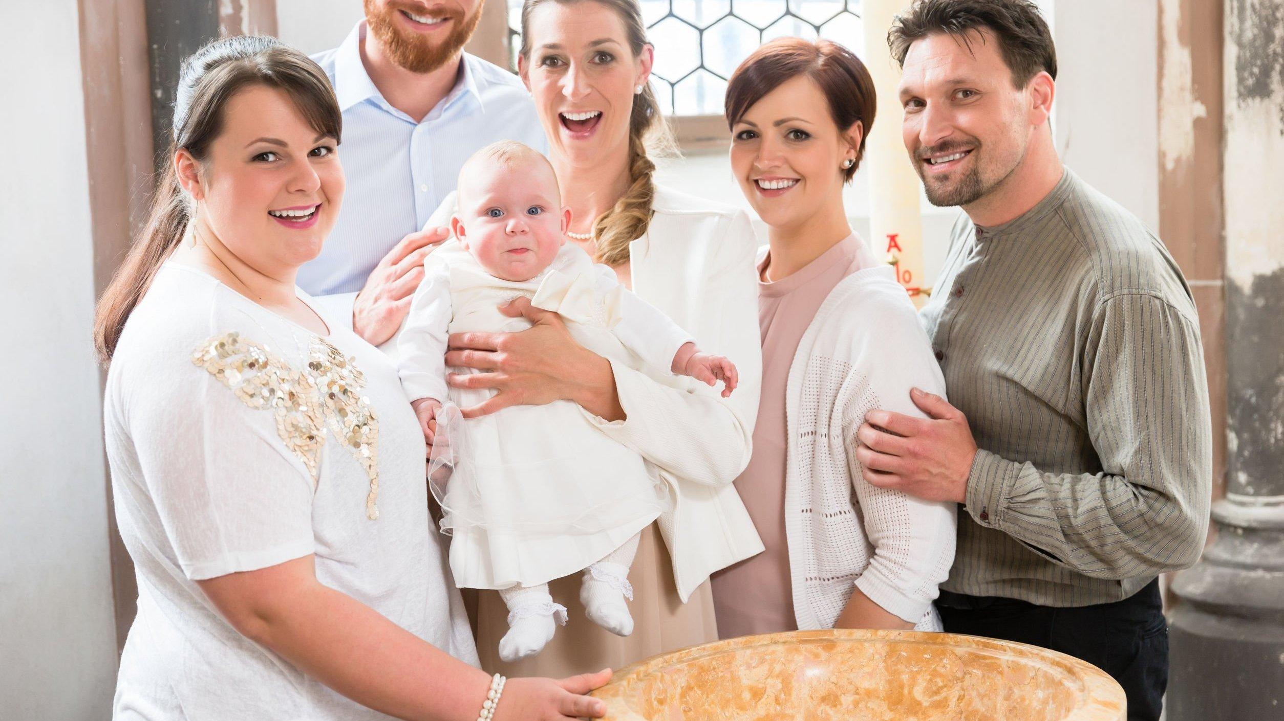 Família sorrindo em batismo. Madrinha segurando neném.