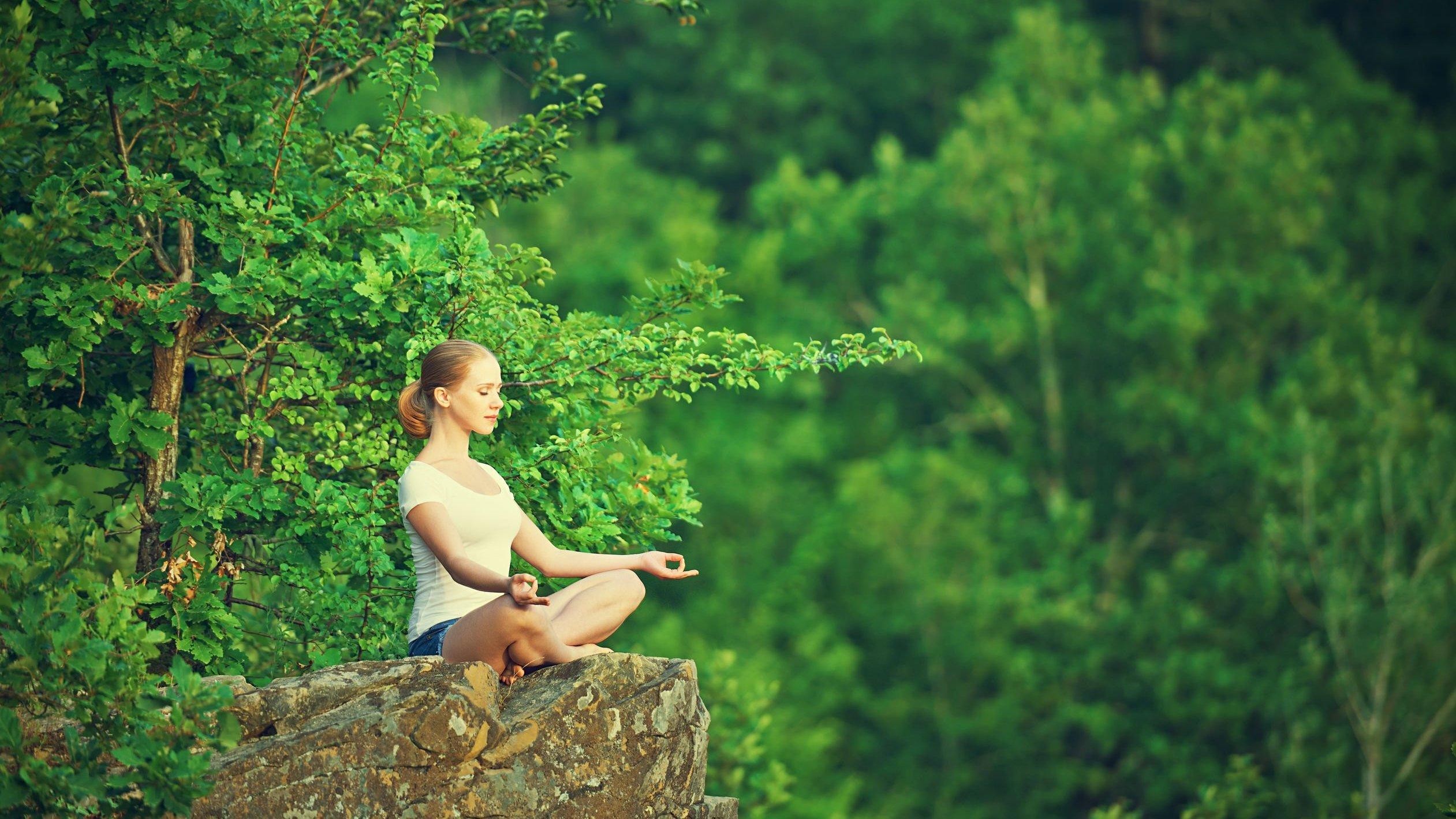 Mulher sentada em pedra, meditando;