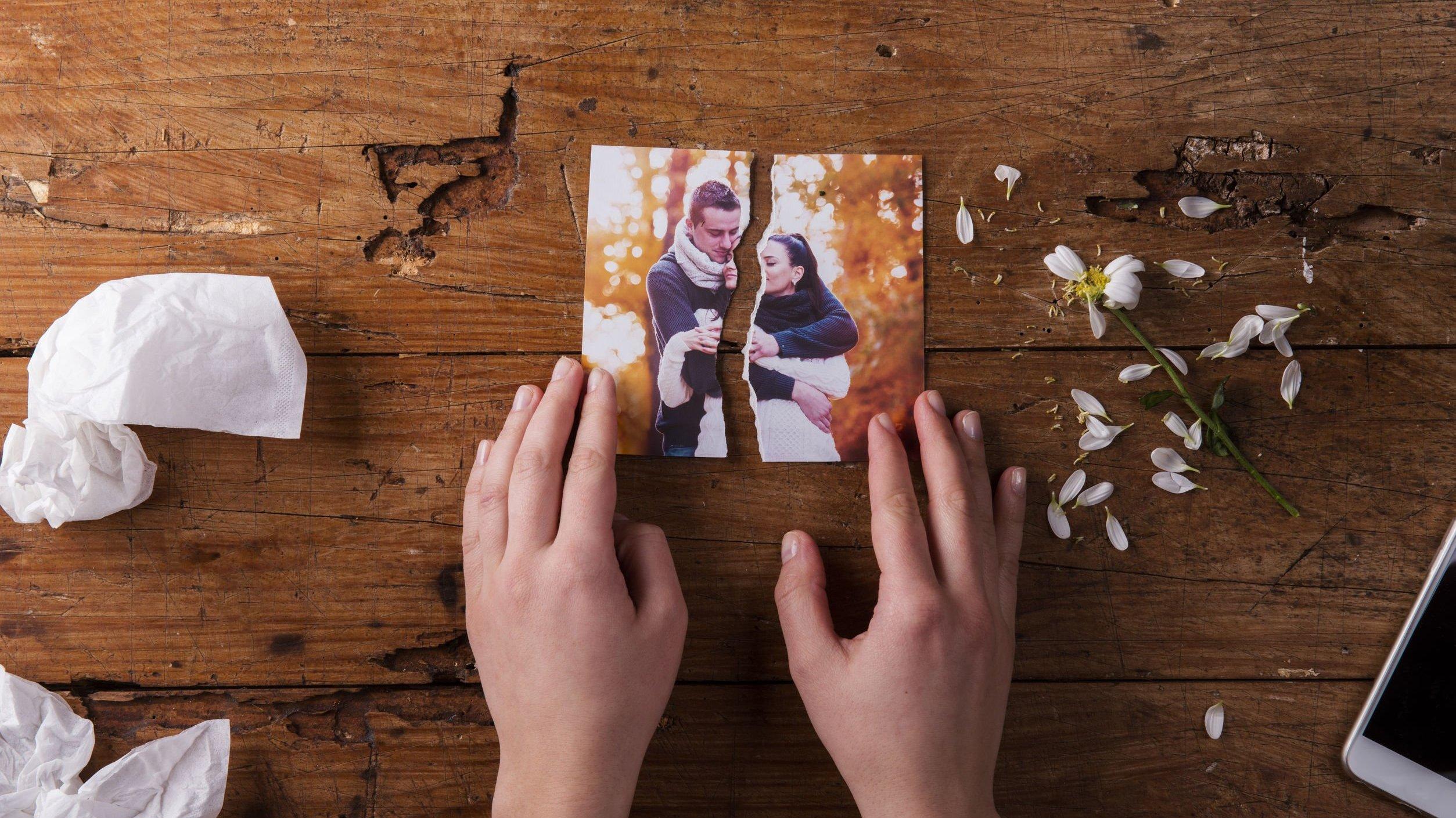 Mão de pessoa segurando foto de namorados rasgada.