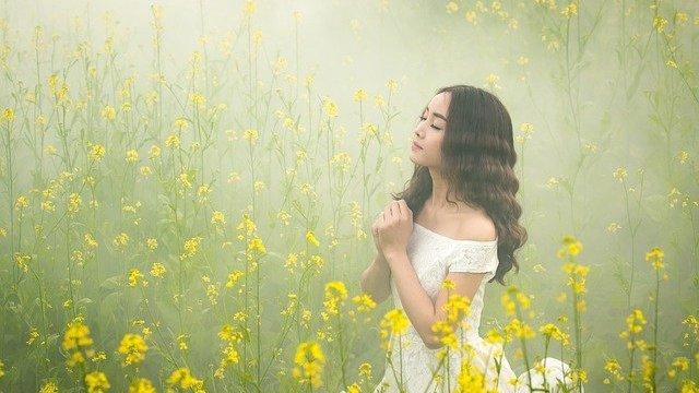 Menina orando em campo de flores