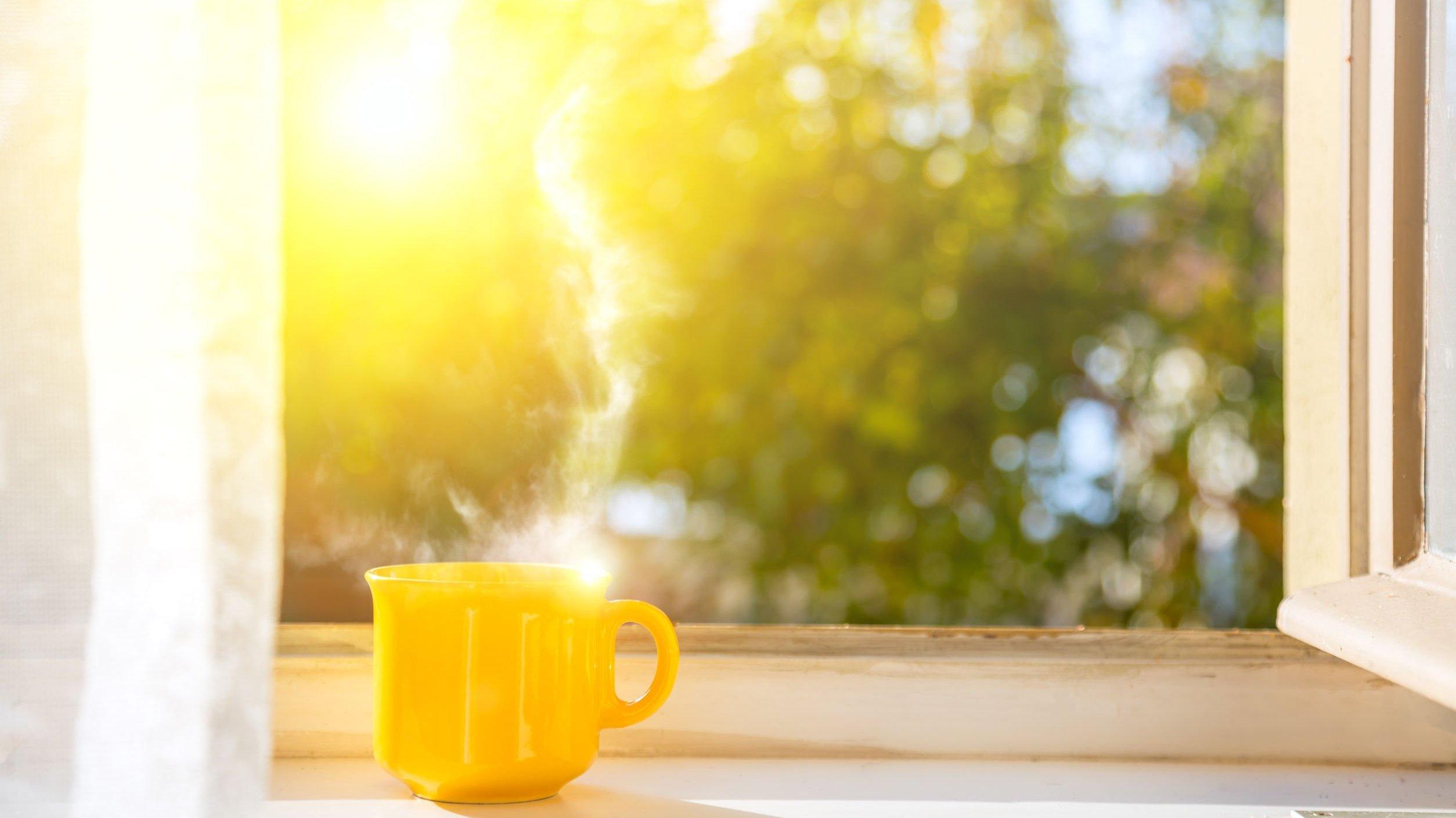 Xícara amarela próxima de janela aberta.