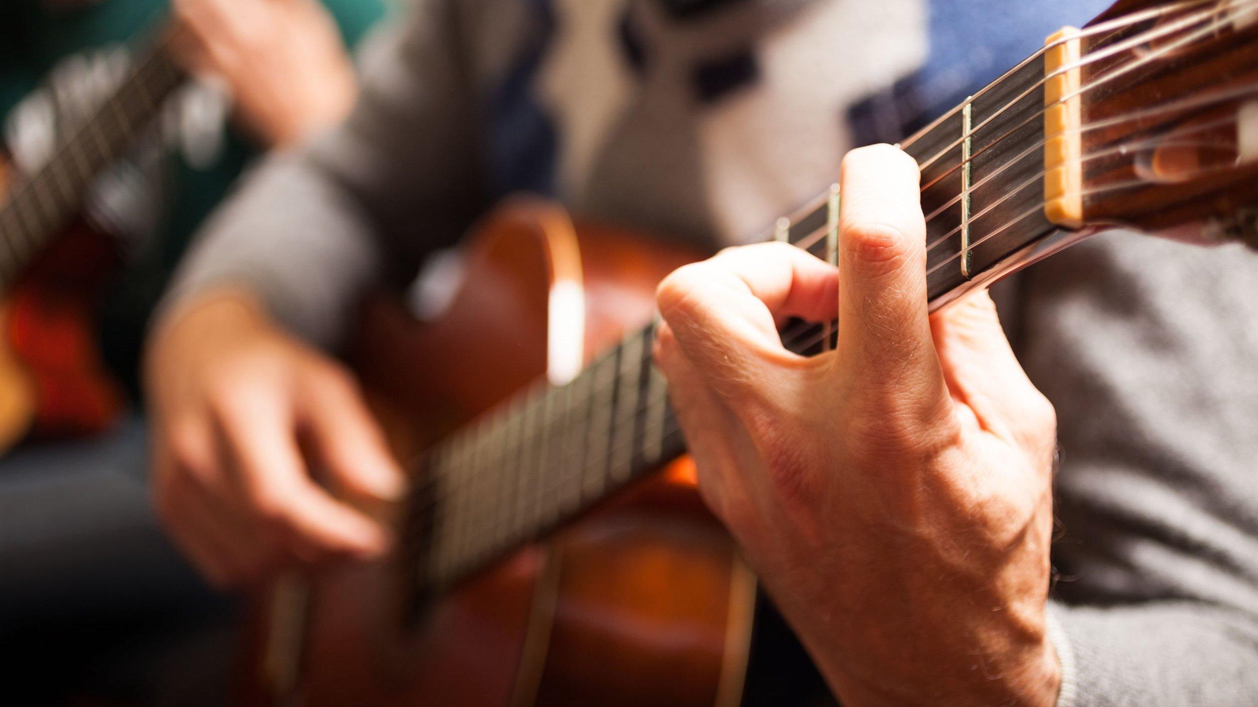 Homem tocando violão.