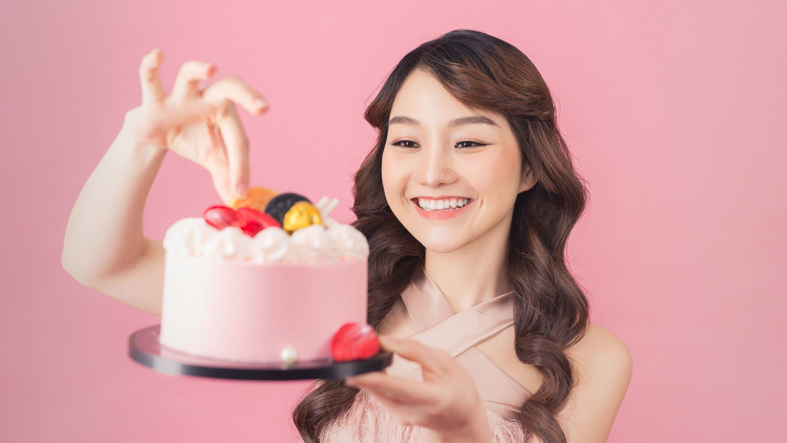 Menina sorrindo, segurando bolo de aniversário.