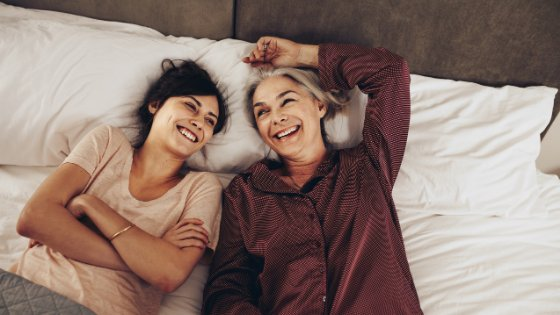 Duas mulheres deitadas na cama sorrindo