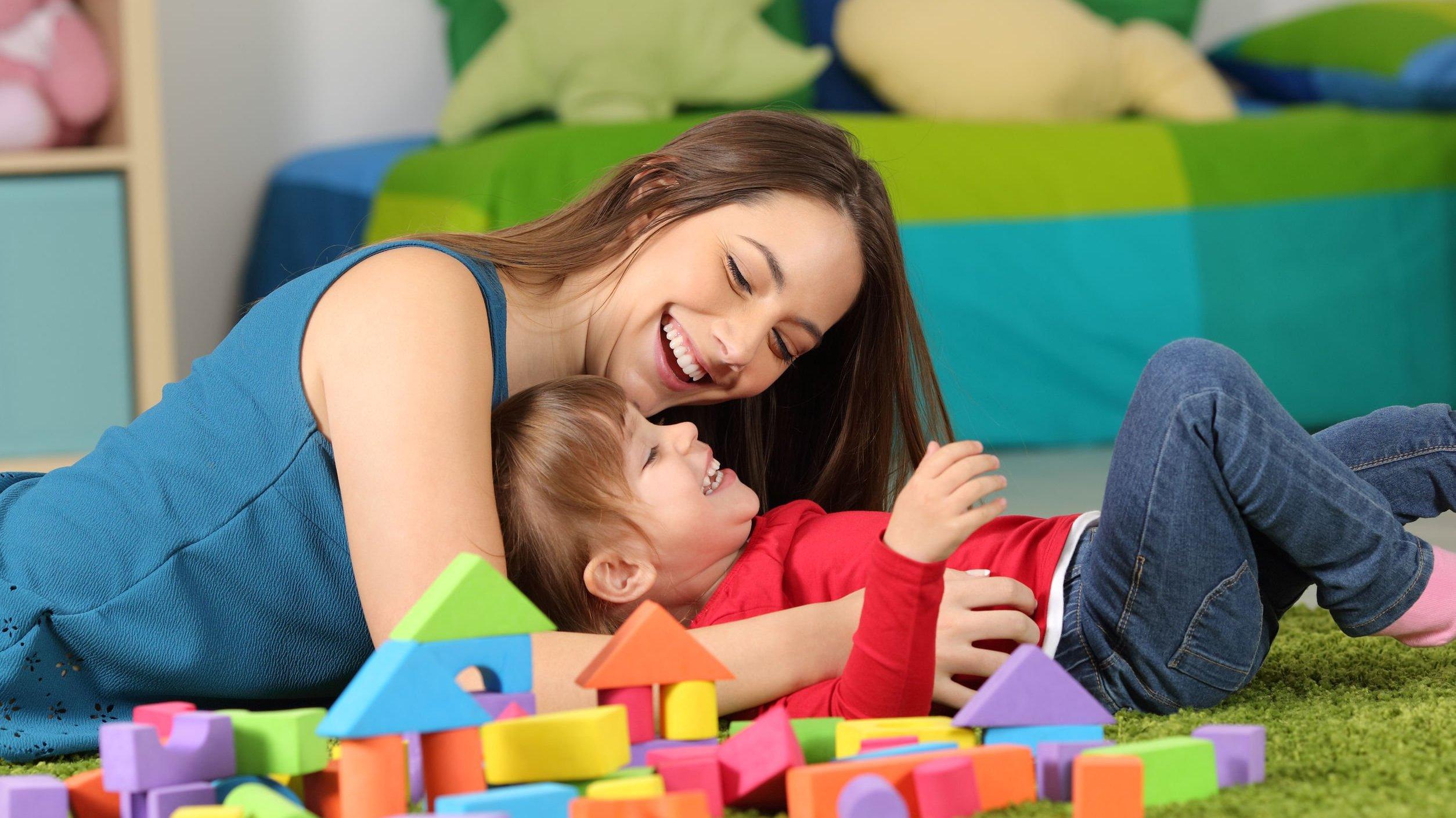 Mulher e criança brincando, dando risada.