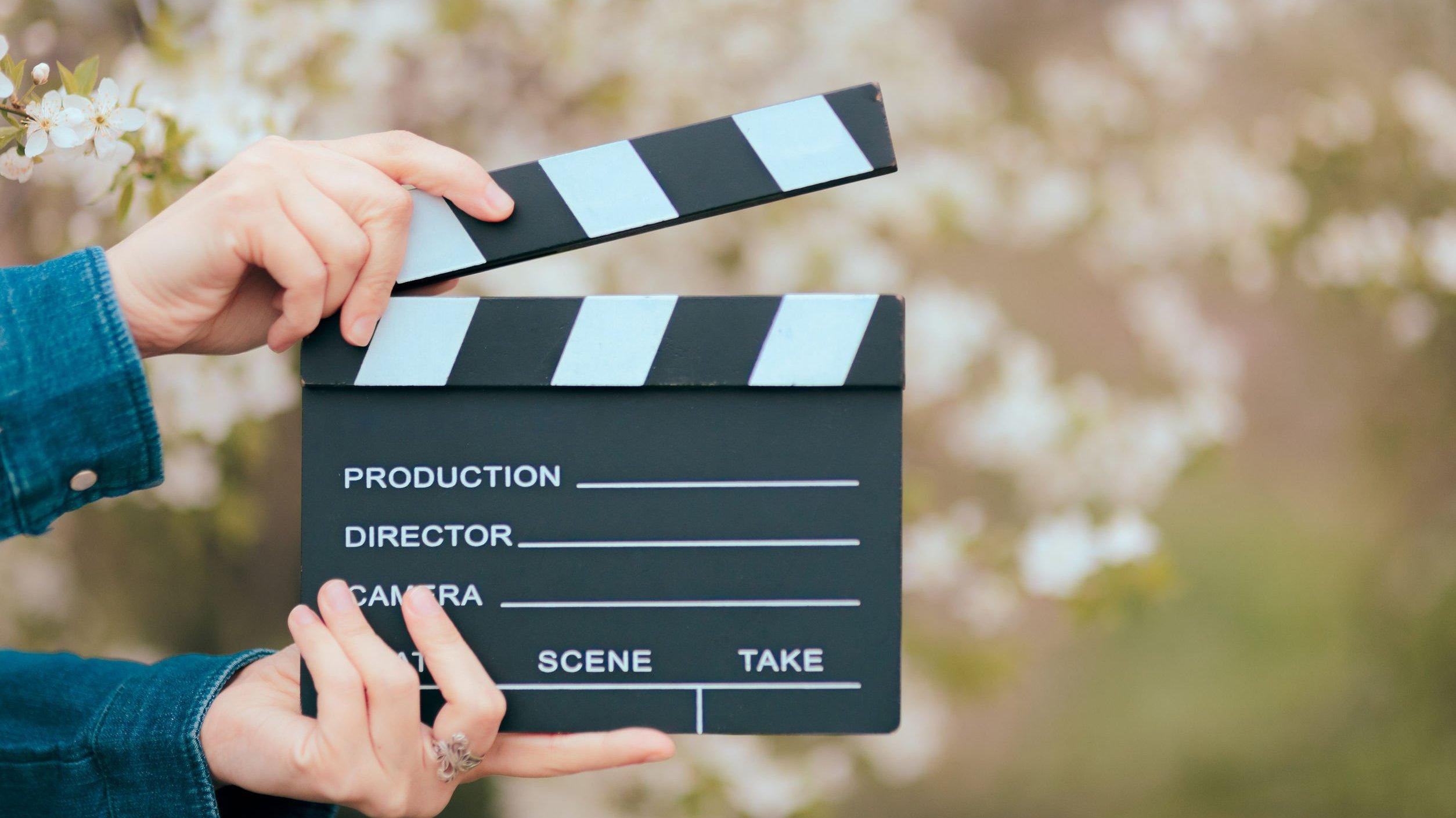 Mãos segurando um filme de ardósia de cinema em fundo de primavera florescendo.