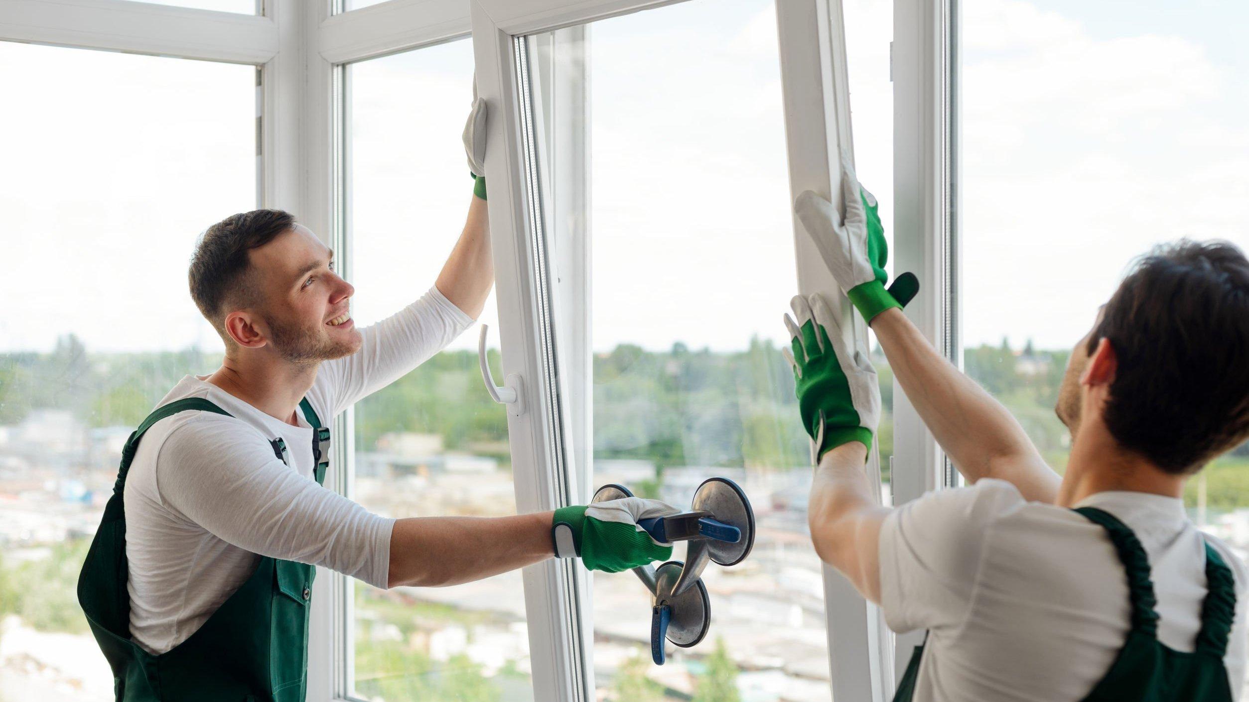 Homens instalando janela de vidro.