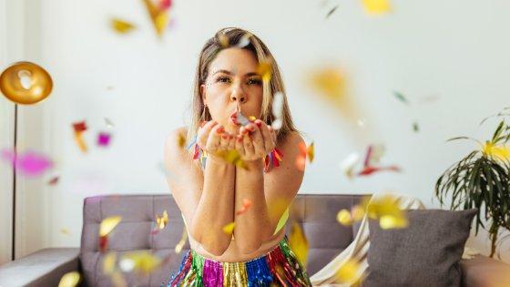 Mulher assoprando confetes coloridos em sua sala