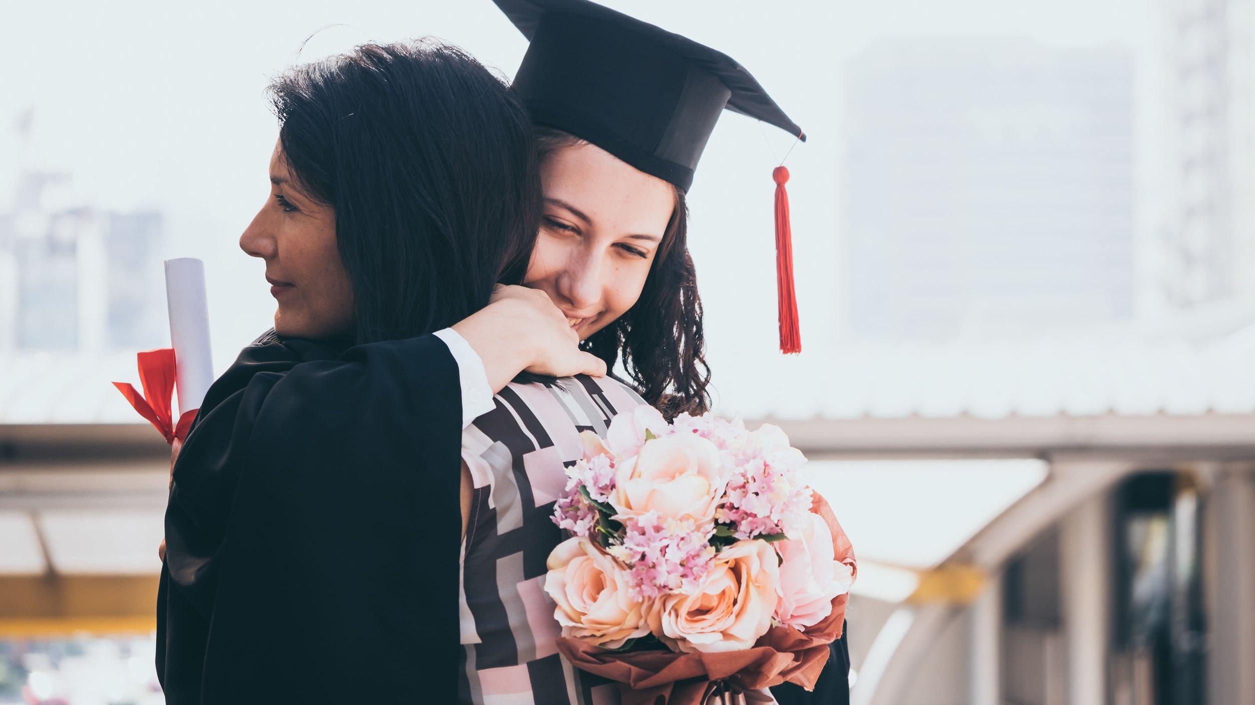Formanda abraçando madrinha de formatura.