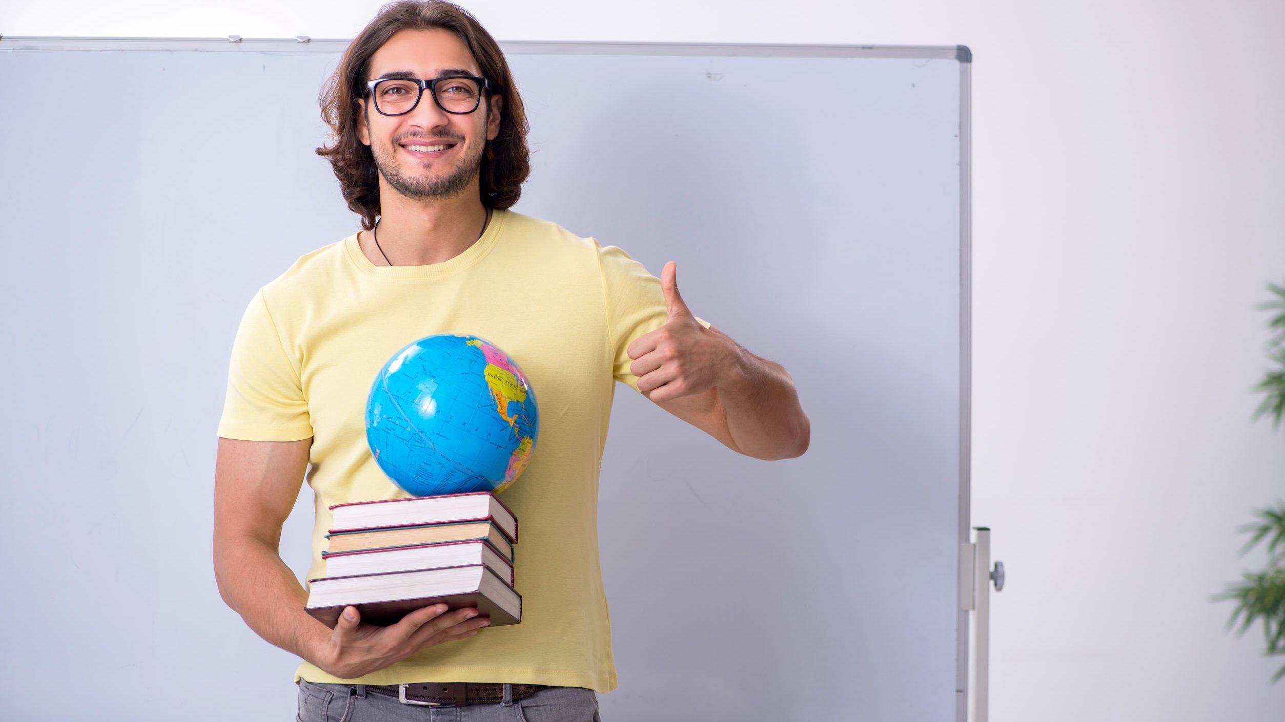 Homem geógrafo sorrindo, segurando livros e globo terrestre.