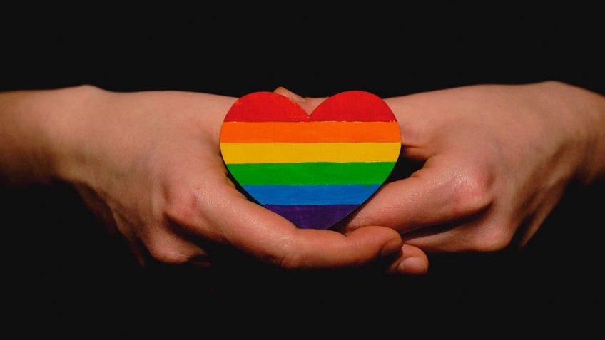Mãos segurando coração estampado com as cores do arco-íris