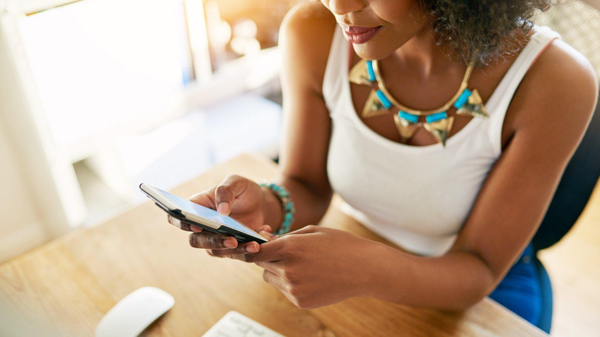 Mulher sentada olhando para o celular